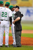 Home plate umpire Marc Lindsey breaks up the conference on the mound against the Clinton LumberKings at Ashford University Field on July 5, 2014 in Clinton, Iowa. The Cougars won 4-0.   (Dennis Hubbard/Four Seam Images)