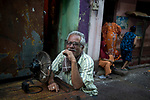 A man enjoys his table fan sitting on a road in soagachi while sec workers shy off from the camera. Soagachi is the lagest red light area in Asia and is economically affected by 21 days lock down in India due to covid 19 pandemic. Kolkata, West Bengal, India. Arindam Mukherjee.