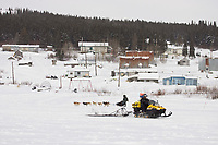 Ramey Smyth passes a trail breaker pulling a trail groomer as he arrives at the White Mountain checkpoint during Iditarod 2008