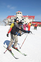 """A man skis downhill while carrying a child in the Club Med Sun Mountain Yabuli Resort, the Club Med's first holiday resort in China. The resort is jointly managed by Melco China Resorts (Holding) Limited & Club Med Asie S.A. (""""Club Med"""")."""