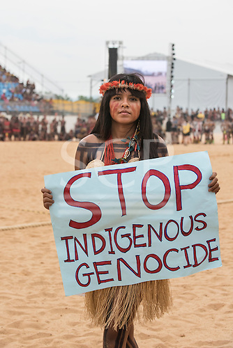 """A Pataxo woman protests against Brazilian government policies on indigenous issues carrying a sign which reads """"stop indigenus genocide"""" during the International Indigenous Games, in the city of Palmas, Tocantins State, Brazil. Photo © Sue Cunningham, pictures@scphotographic.com 25th October 2015"""