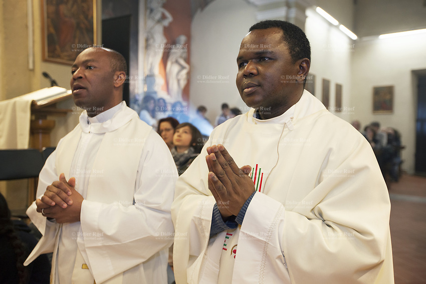 """Switzerland. Canton Ticino. Grancia. Church «San Christoforo». Don Gerald Chukwudi Ani (R) and Don Stanley Orazurike (L) are both catholic priests from Nigeria (Africa). They are celebrating the holy Mass of the Lord's Supper, also known as A Service of Worship for Maundy Thursday, which is a Holy Week service celebrated on the evening of Maundy Thursday.It inaugurates the Easter Triduum and commemorates the Last Supper of Jesus with his disciples, more explicitly than other celebrations of the Mass. The Mass stresses three aspects of that event: """"the institution of the Eucharist, the institution of the ministerial priesthood, and the commandment of brotherly love that Jesus gave after washing the feet of his disciples. Easter Triduum is the period of three days that begins with the liturgy on the evening of Maundy Thursday, reaches its high point in the Easter Vigil, and closes with evening prayer on Easter Sunday. 29.03.2018 © 2018 Didier Ruef"""