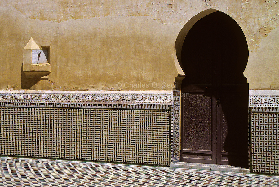 """Meknes, Morocco.  Mausoleum of Moulay Ismail.  Horseshoe Arch Doorway and Sun Dial.  The Arabic calligraphic frieze surrounding the courtyard reads """"'Auzu b'illah"""" (""""I seek refuge in God."""")."""
