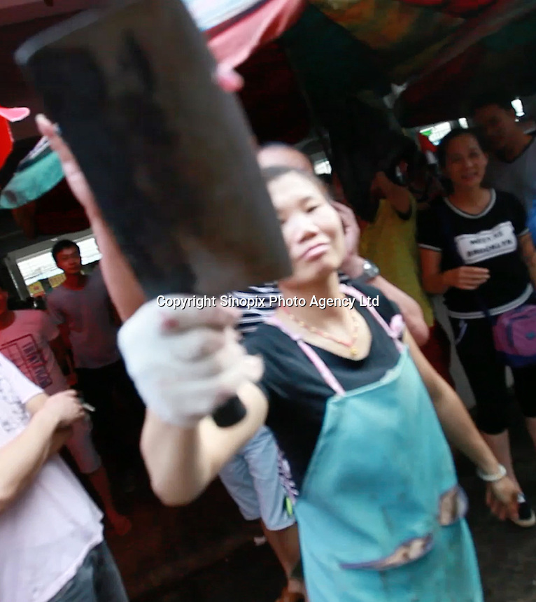 Locals stop photograper taking images at Yuilin, one day before the Yulin Dog Meat Festival kicks off, Yulin, Guangxi Province, China, 20 June 2016.<br /> <br /> photo by str/Sinopix