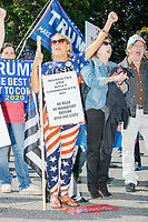 People hold pro-Trump, pro-police, anti-vaccine, and anti-mask signs as alt-right organization Super Happy Fun America demonstrates against facemasks, vaccines, and pandemic closures, and in support of the reelection of President Donald J. Trump near the residence of Massachusetts governor Charlie Baker in Swampscott, Massachusetts, on Sat., Sept. 26, 2020. Super Happy Fun America is most well known for organizing the Straight Pride Parade in Boston on August 31, 2019.