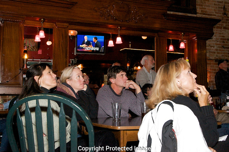 Interested voters gather in the Waterside Brewery to watch the last debate between Barack Obama and John McCain. The TV monitor is seen reflected in a mirror.