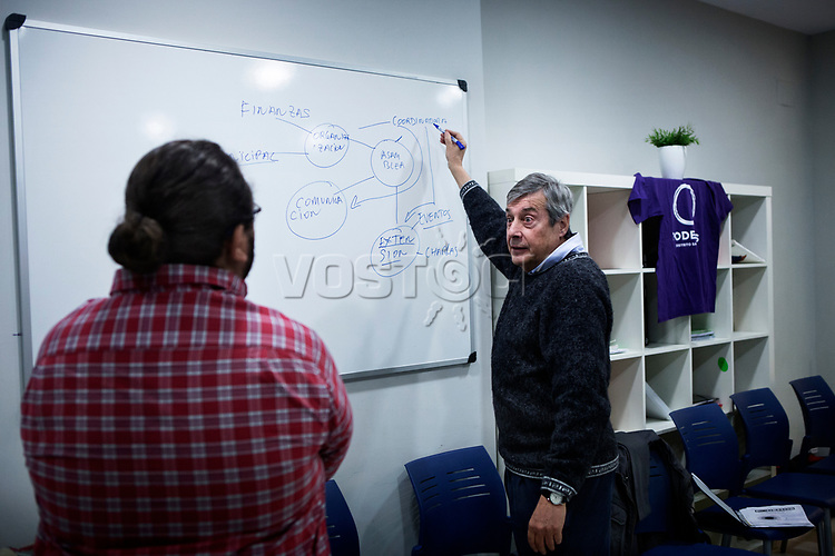 Madrid, Spain, February 12, 2015. A member of the left wing [party] Podemos explains to a newcomer the workflow of the political organisation before a meeting in Salamanca's neighbourhood in Madrid.