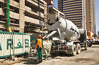 Ready mixed concrete truck fills crane skip during the construction of a high rise tower block.  Dubai. United Arab Emirates.
