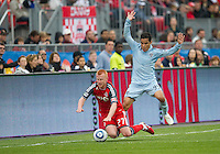 Sporting KC forward Omar Bravo #99 and Toronto FC defender Richard Eckersley #27 in action during an MLS game between Sporting Kansas City and the Toronto FC at BMO Field in Toronto on June 4, 2011...
