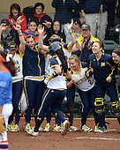 Michigan Wolverines players including utility player Kelsey Susalla (7) and outfielder Brandi Virgil (2) celebrate as shortstop Sierra Romero (32) touches home after hitting a grand slam home run during the season opener against the Florida Gators on February 8, 2014 at the USF Softball Stadium in Tampa, Florida.  Florida defeated Michigan 9-4 in extra innings.  (Copyright Mike Janes Photography)