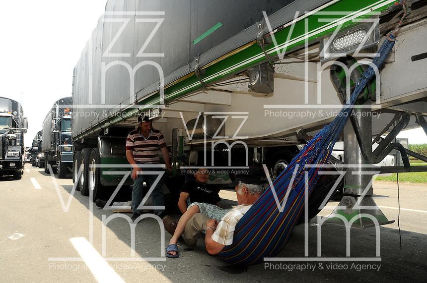 VILLA  RICA - COLOMBIA - 06-03-2013: Cientos de camiones se encuentran estacionados en la carretera Panamericana en la población de Villa Rica al norte del departamento del Cauca, marzo 06 de 2013. La vía Panamericana en el sur del país se encuentra bloqueda en varios sitios, obstaculizando la movilización de vehículos, causando desabastecimiento de alimentos y aislamiento, el paro de caficultores lleva más de una semana (Foto: VizzorImage / Luis Ramírez / Staff). Hundreds of trucks are parked on the Panamerican highway in the town of Villa Rica in northern Cauca, March 6, 2013. The Panamerican Highway in the south of the country is blocked in several places, causing food shortages and isolation, unemployment of farmers takes more than a week (Photo: VizzorImage / Luis Ramirez / Staff).