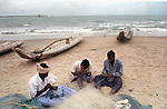 Fishermen weaving nets in preparation for their return to the sea.Nagapattinam.India.
