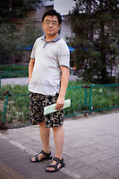 Fangdiezhen, an independent worker, age 45, poses for a portrait in Beijing. Response to 'What does China mean to you?': 'Central country'  Response to 'What is your role in China's future?': '[I] will have a bigger and bigger impact.'