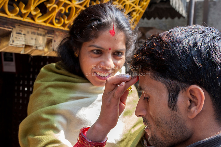 Nepal, Kathmandu.  Woman Applying a Bindi of Kumkuma Powder to a Friend's Forehead before Praying at the Ashok Binayak (Maru Ganesh) Temple, Durbar Square.