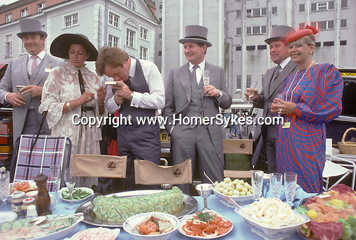 """Derby Day Epsom Downs. The English Season published by Pavilon Books 1987. Picnic in car park Typical 1980s fashion mens suits have been hired from Moss Bross, women wear """"power shoulders"""""""