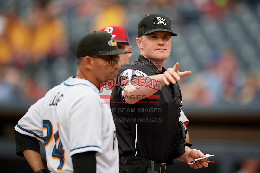 Umpire Thomas Roche during the lineup exchange with Rouglas Odor (24) and Sean Williams (back) before an Eastern League game between the Reading Fightin Phils and Akron RubberDucks on June 4, 2019 at Canal Park in Akron, Ohio.  Akron defeated Reading 8-5.  (Mike Janes/Four Seam Images)