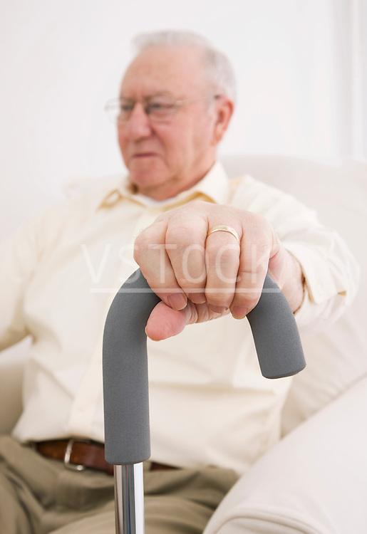 Senior man with hand on walking cane, close-up