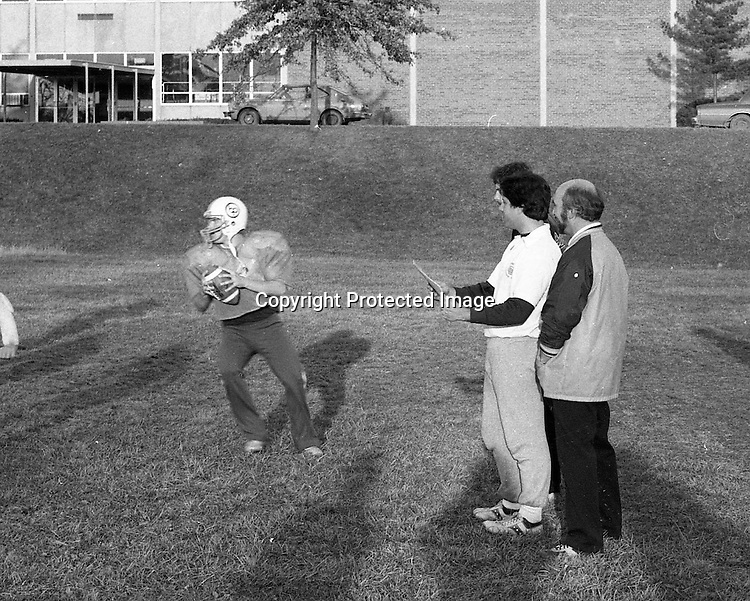 Bethel Park PA:  Bethel Park High School Football Coaches Gerry Runco, Don Porter, and Chuck Boig, watching Shawn Morton at Practice.<br /> Notable players included; future college and NBA star Armen Gilliam (DE), Shawn Morton QB, Steve Berlin (T), Eric Coss (T), Van Richardson (LB), Evan Evanovich (TE).<br /> The team made a great run in the WPIAL AAAA playoffs beating the #2 rated high school football team in the nation, North Hills in 3 overtimes, and then top 5 Gateway the next week.  Came up a little short against Mt Lebanon in the championship game at Pitt Stadium.<br /> Coaches included Head Coach & OC Bob King, Don Porter (DC), Dave George (LB, TE), Leo Henne (DL), Dave Luptak (R, DB), Gerard Runco (R, Secondary), Chuck Boig (QB, DB) and Mike Stewart (RB, DB).