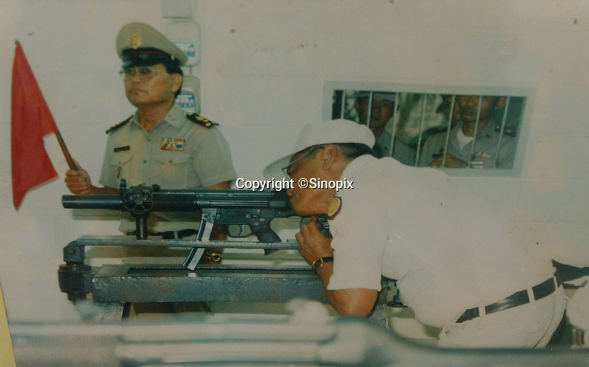 Thailand's only executioner Chawalate Jarubun of Bangkwang Central Prison fires a machine gun during an execution.  Jarubun has executed 55 prisoners.