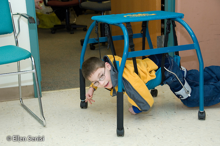 MR / Albany, NY.Langan School at Center for Disability Services .Ungraded private school which serves individuals with multiple disabilities.Child uses a belly crawler as he crawls down the hall. Student is weaing a SWASH (sitting, walking and standing hip aparatus) on his hips / legs. Boy: 9, cerebral palsy, limited verbal output with expressive and receptive language delays.MR: Rub1.© Ellen B. Senisi
