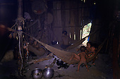 Roraima, Brazil. Yanomami family inside of a shabore with an open fire.