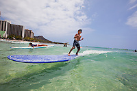 Young boy surfing in Waikiki on a long board
