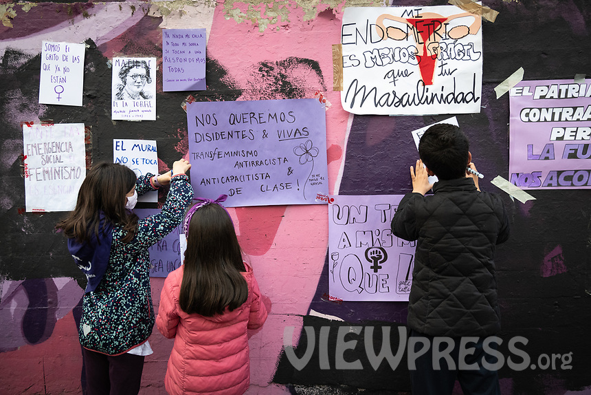 "MADRID, SPAIN – MARCH 08: Some children writing posters with the message ""the mural is not touched"" in front of the feminist mural that has been sabotaged the night before 8M in the Ciudad Lineal neighborhood on 8 march in Madrid, Spain. Various demonstrations and protests have been carried out to celebrate and commemorate the international day of working women that is celebrated every year on March 8. (Photo by Joan Amengual / VIEWpress via Getty Images)"