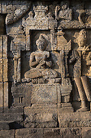 """Borobudur, Java, Indonesia.  Stone Carving Showing Scenes from the Buddha's Life, North Face.  Here the Buddha Makes the Dharmachakra Mudra, """"rolling the wheel of dharma"""" or the law."""