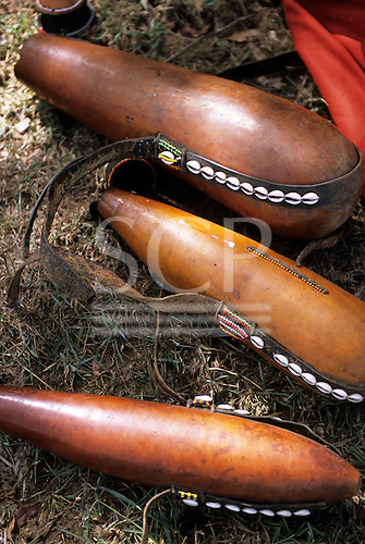 Lolgorian, Kenya. Siria Maasai gourds for milk collecting, leather straps decorated with beads and shells. Cucurbitaceae; Lagenaria siceraria.