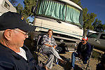 """ANDRADE, CA, U.S.-March 24: Tom Parker (L) ,70,Angela Key (C), 60 and her husband John, 70 enjoy the morning sunshine outside Parker's RV just down the road from the border crossing to Algodones, Mexico march 24, 2005. All three have had medical treatment in Algodones. Angela Key said, """"I'd love for the people that decide what they give you [for retirement] to try live on what we get."""" Visiting Algodones helps them make ends meet.  ©Radhika Chalasani"""