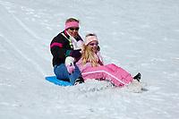 Mother and Daughter sledding Hawaiian style on their body board Mauna Kea The Big Island of Hawaii