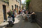 Columbia Road Sunday Flower Market East London Uk. A street off the flower market people enjoy summer weather in Hackney.
