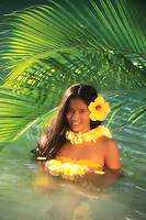 Young woman with plumeria, hibiscus and palm leaves