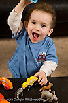 2 year old toddler boy at home portrait language development vocalizing talking holding up toy vertical