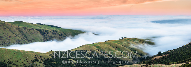 Rolling clouds over farmland on Banks Peninsula. Pacific Ocean under layer of clouds, Canterbury, South Island, New Zealand