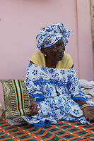 Senegal, Saint Louis.  Old Senegalese Woman with Fan Sitting on her Front Porch.