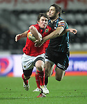 Ian Keatley tries to get away from Andrew Bishop..RaboDirect Pro12.Ospreys v Munster.Liberty Stadium.03.12.11.©Steve Pope
