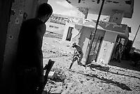 Anti-Gaddafi fighter runs to engage a Gaddafi loyalist position in Sirte, Libya.