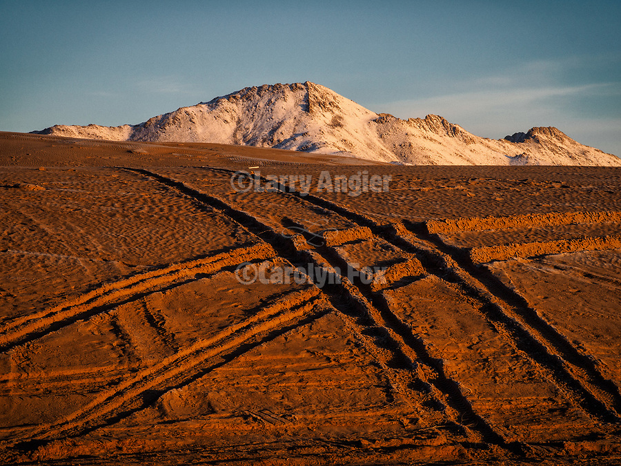 Tire tracks at sunrise at the Winnemucca Dunes along US-95 north of town in the late winter. Snow covering the Santa Rosa Range.