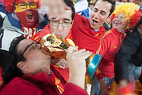 Spanish fans kiss a replica statue of the FIFA World Cup trophy after Spain won the 2010 FIFA World Cup Final.   Spain played Holland at Soccer City in Soweto, South Africa on Sunday, July 11, 2010.  Spain defeated Netherlands 1-0.