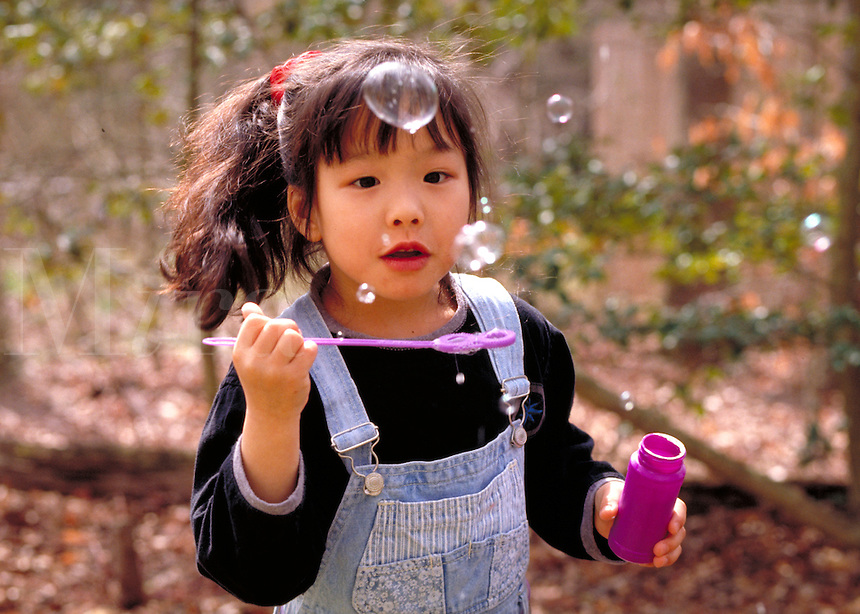 5 year old asian-american girl playing with soap bubble. Kids, fun, children. Kimberly.