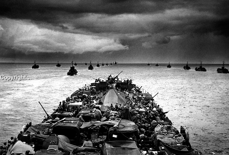 Columns of troop-packed LCIs trail in the wake of a Coast Guard-manned LST en route for the invasion of Cape Sansapor, New Guinea.  The deck of the LST is closely packed with motorized fighting equipment.  1944. PhoM1c. Harry R. Watson. (Coast Guard)<br /> Exact Date Shot Unknown<br /> NARA FILE #:  026-G-2839<br /> WAR & CONFLICT BOOK #:  1163
