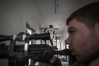 In this Tuesday, Oct. 30, 2012 photo, rebel fighters belonging to the Liwa Al-Fatah keep an eye on their enemy position from a school building during skirmishes with the Syrian army in the nearby Bustan Al-Pasha front line in Aleppo, Syrian's largest city. (AP Photo/Narciso Contreras).