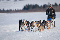 Lance Mackey runs on the Fish River just before his arrival into White Mountain during Iditarod 2009