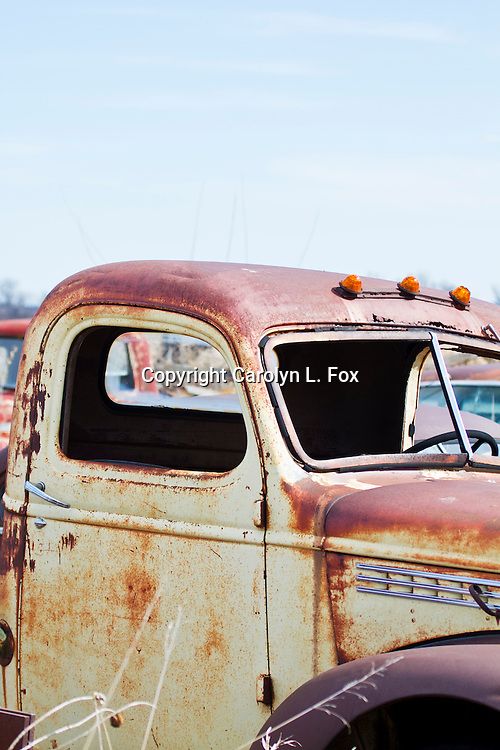 An old, rusty truck sits in a junk yard.