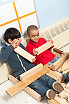 Education preschool two boys playing game with wooden block construction working together holding blocks and talking