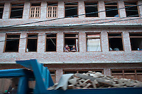 Two women on a window of a damaged house in Bhaktapur, near Kathmandu, Nepal. May 04, 2015