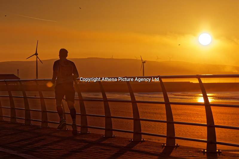 A man jogs on the promenade as the sun rises over Swansea Bay in south Wales, UK. Tuesday 26 February 2019