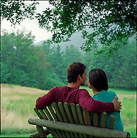 Couple, sitting on bench with backs to camera