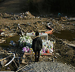 On March 11, 2011, the earthquake of magnitude 9.0, the biggest earthquake in the history of Japan and the fourth biggest earthquake in the world after year 1900, shocked the Tohoku area of Japan. In about 30 minutes, devastating tsunami reached, affecting the coastline with a length of 500 km (310 miles). The tsunami wave height of 39 meters (128 feet) was recorded in a port town in Tohoku. The tsunami swallowed villages along the coast and washed away all houses. The earthquake and tsunami killed more than 15,800 people, and still more than 3,500 people are missing. <br /> <br /> A woman stands in front of the gate of Okawa Elementary School in Ishinomaki, Miyagi, in one month after the earthquake and tsunami. 74 children out of 108 students and 10 of 11 teachers who were in the school at that time were killed by the tsunami. They were trying to evacuate all together to a higher place 200 meters away from the school when the tsunami came over the river's bank and swallowed them. Flowers and sweets are placed for the children who lost their lives.